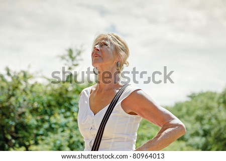 Single senior blond woman dressed in white enjoying nature on summer day.