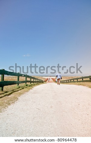 Single senior man walking on path to the beach on hot summer day with clear blue sky.