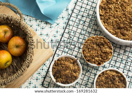 Single serving and larger dish of apple crumble cooling on rack, viewed from above - stock photo