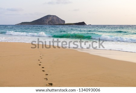 Single set of footprints leading to the ocean at Makapuu Beach with Manana and Kaohikaipu Islands (Rabbit Island and Turtle Island) in the distance, Oahu, Hawaii - stock photo