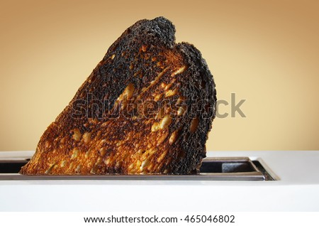 Single slice of burnt toast jumping out of a white toaster