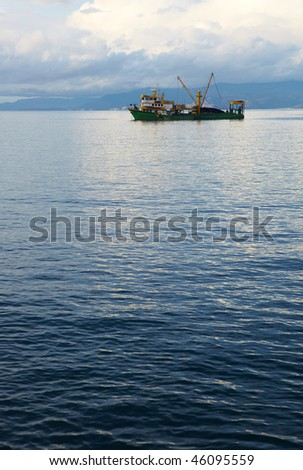 Single small fishing trawler leaving the harbor into the the blue Aegean sea to go fishing on a cloudy winter's day.