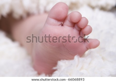 single small newborn baby foot on soft blanket