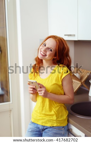 Single smiling cute red head holding smart phone with tilted head while leaning back against kitchen counter - stock photo
