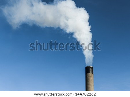 Single smoke stack against a blue sky.