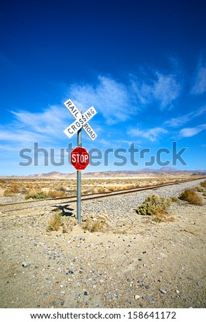 Single stop sign and railroad crossing stands lonely beside an unused stretch of rail in California's Mojave Desert.