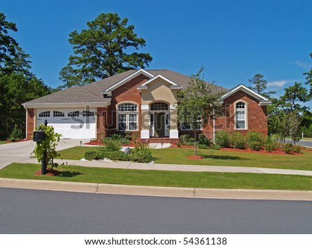 Single story brick residential home with the garage in the front. - stock photo