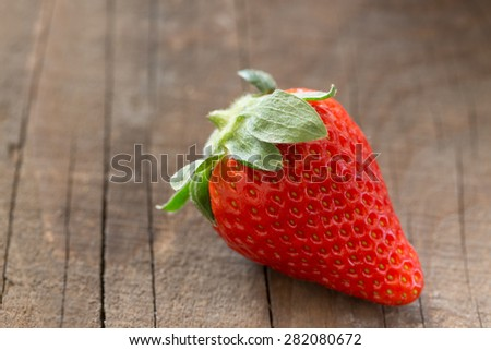 Single Strawberry on a rustic wooden background - stock photo
