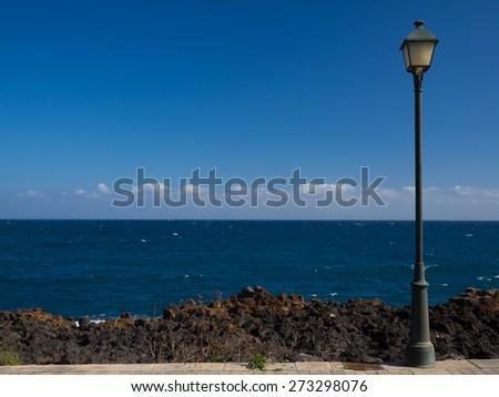 Single street lamp on the promenade overlooking the sea - stock photo