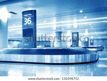 Single suitcase alone on airport carousel - stock photo