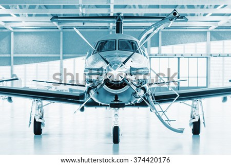 Single turboprop aircraft in big hangar. Focus on nose aircraft, colored on technical blue. - stock photo