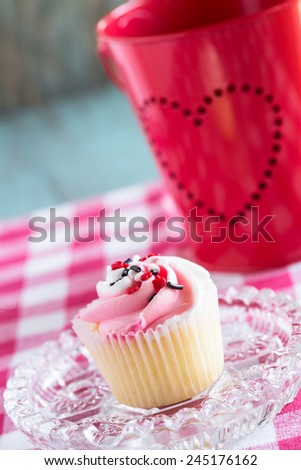 Single Valentines Day cupcake on plate with tin heart bucket