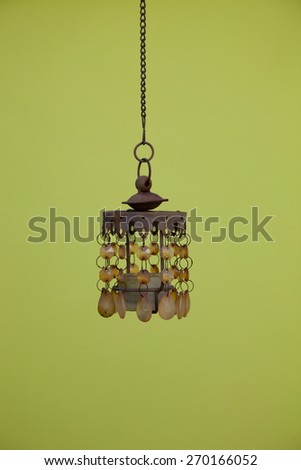Single Vintage Hanging Shell Pendant Light with Chain Isolated on Dark Yellow Green Background