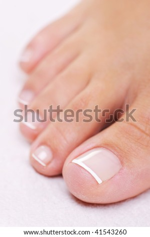 Single well-groomed female foot with a french pedicure. Close-up toy. - stock photo