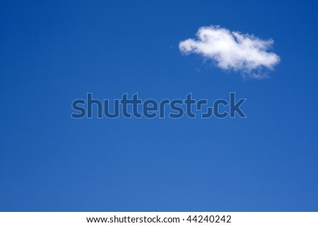 Single white fluffy cumulus cloud against a blue sky - stock photo
