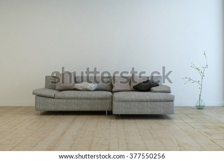 Single wide gray sofa with pillows on top next to bare tree houseplant on wooden floor in empty room - stock photo