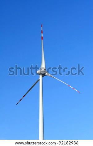 Single wind turbine on blue sky - stock photo