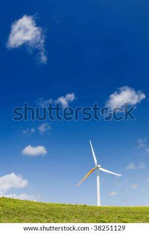 Single wind turbine on grassy field over deep blue sky, alternative energy, green power, electricity generator - stock photo