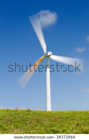 Single wind turbine on grassy field over deep blue sky, alternative energy, green power, electricity generator. Long exposure to show spinning motion, blurred blades. - stock photo