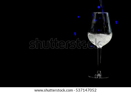 Single wine glass on black background with blue bokeh