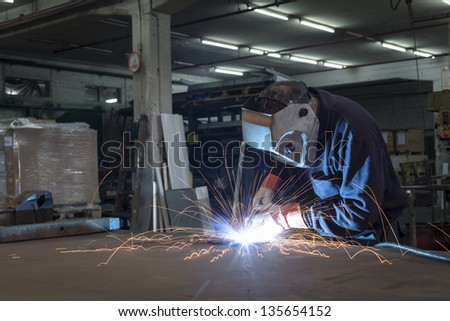 Single worker welding working in a steel factory with sparks flying