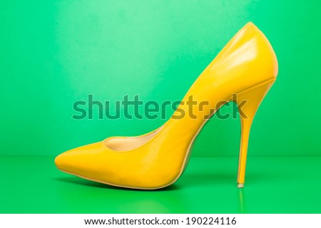 single yellow high heels on green background - stock photo