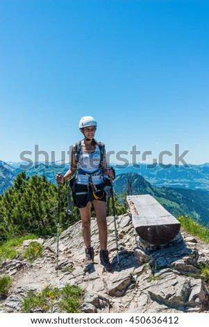 Single young adult woman in white helmet, shorts and tee shirt with confident expression, holding hiking sticks as she stands beside log bench at mountain summit - stock photo