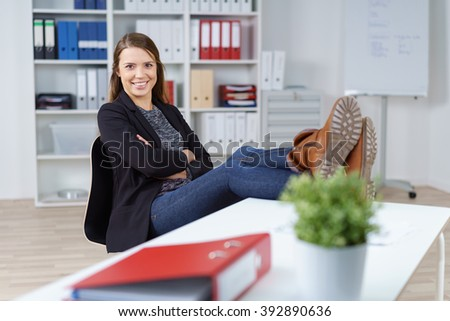Single young female confident office worker in black jacket with feet on table that has notebook and plant in foreground - stock photo
