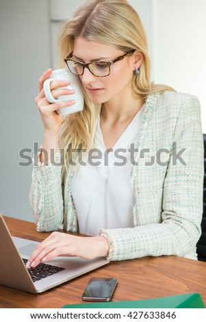 Single young professional blond woman wearing eyeglasses at brown wooden desk with open laptop and cell phone drinking coffee - stock photo
