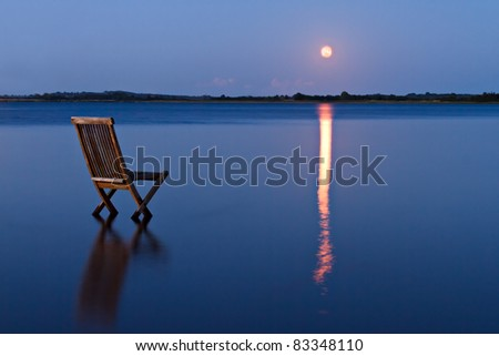 Singular chair in calm water facing the land in the horizon. With rising orange moon reflected in the blue water - stock photo