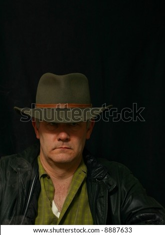 Sinister and somber portrait of unshaved man on black background - stock photo