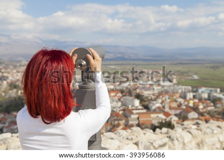 Sinj, Croatia, Woman with red hair looking through a coin operated binoculars, rear view - stock photo