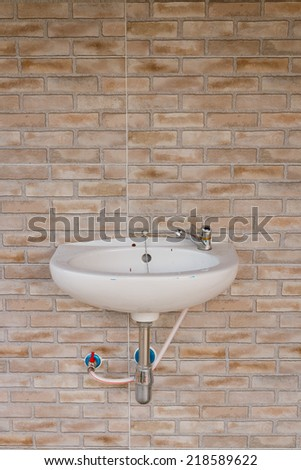 sink and tap on brick background - stock photo