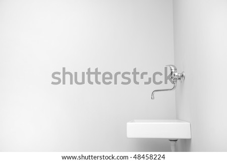 Sink in an empty big white room. - stock photo