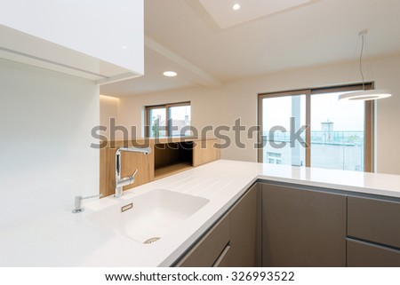 Sink with tap on white worktop of contemporary kitchen - stock photo