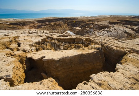 Sinkholes or open pit on the shore's of the dead sea at the end of the summer when the water level is at it's lowest - stock photo