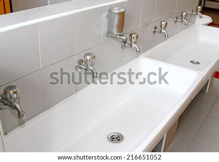 sinks and washbasins with very low taps in the toilets of a nursery