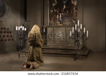 Sinner prays in medieval church - stock photo
