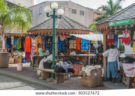 Sint Maarten, Philipsburg-June 3: Vendors unpack goods at Market Place on June 3, 2008. The island is a major center for tourism, duty free shopping and sailing regattas in the Caribbean. - stock photo