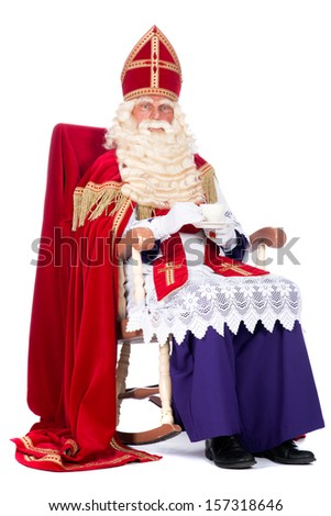 Sinterklaas is resting on his chair, drinking a cup of coffee - stock photo