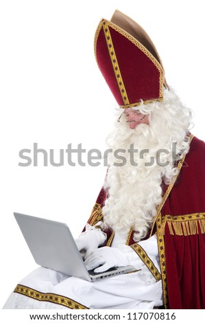 Sinterklaas using a laptop in stead of his book