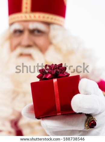 sinterklaas  with gift . typical Dutch character part of a traditional event celebrating the birthday of Sinterklaas (Santa Claus) in december.Selective focus on gift - stock photo