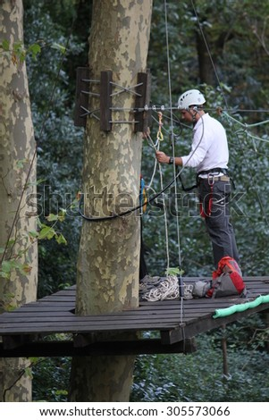 SINTRA, PORTUGAL - OCTOBER 25 2014: Man on an elevated platform at work cleaning a tall tree in Castle of the Moors garden