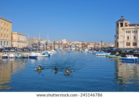 SIRACUSA, ITALY - JENUARY 17: fishing boats and kayakers in the darsena of Ortigia Islet from the Bridge Umbertino. On the background the skyline of Siracusa on the mainland. Shot in 2015 - stock photo