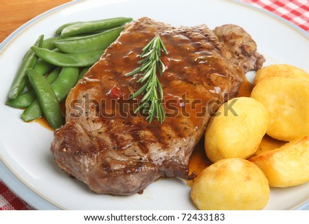 Sirloin beef steak with roast potatoes and sugar snap peas. - stock photo