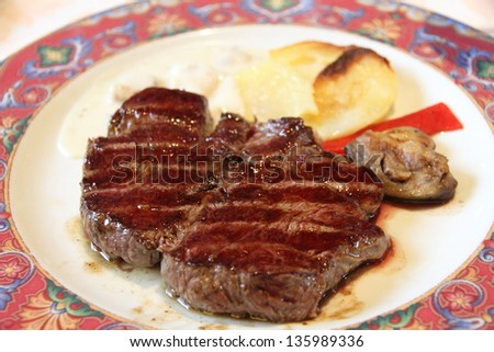 sirloin steak on white plate with vegetables