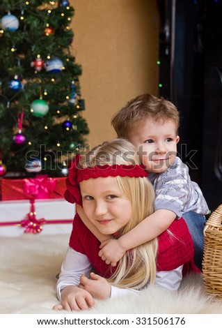 Sister and brother at Christmas fir tree and fireplace