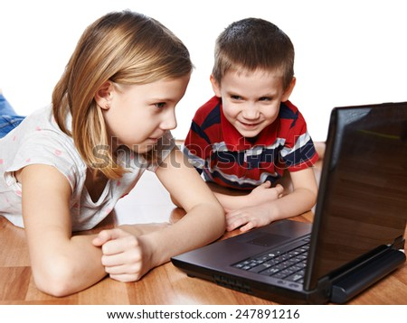 Sister and brother looking to laptop lying on the floor - stock photo