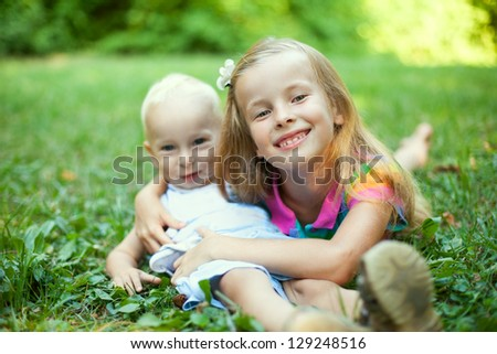 Sister and brother lying on green grass in summer