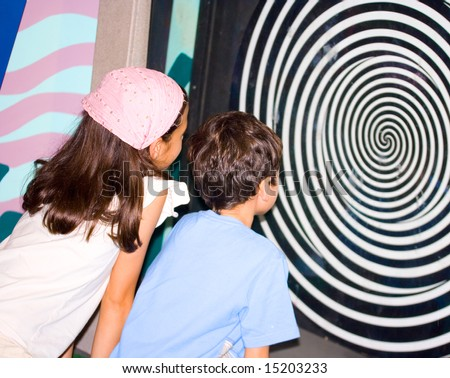 Sister and brother observing the optical illusion swirl at the science centre - stock photo